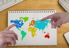 Hands pointing at America and Russia on Colorful Map on a notepad. Digital composite of Hands pointing at America and Russia on Colorful Map on a notepad royalty free stock photos