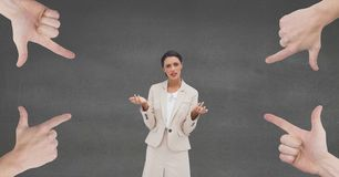 Hands pointing at confused business woman against grey background. Digital composite of Hands pointing at confused business woman against grey background Stock Photo