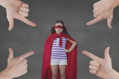 Hands pointing at girl in a super heroine custom against grey background royalty free stock photo