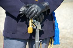 Hands of policeman. Particular policeman in uniform with sword stock image