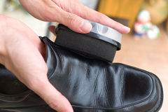 Hands polish leather black shoes. Royalty Free Stock Photo