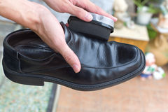 Hands polish leather black shoes. Royalty Free Stock Image