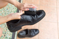 Hands polish leather black shoes. Royalty Free Stock Photography