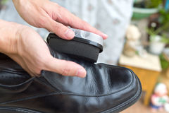 Hands polish leather black shoes. Royalty Free Stock Photos