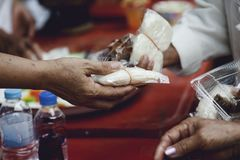 Hands of the poor receive food from the donor`s share. poverty concept.  royalty free stock image