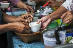 Hands of the poor receive food from the donor`s share. poverty concept. Feeding the poor to help and share royalty free stock image