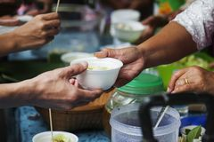 Hands of the poor receive food from the donor`s share. poverty concept. Feeding the poor to help and share stock images