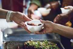 Hands of the poor receive food from the donor`s share. poverty concept. Feeding to hand the poor helping beggar in social. poverty concept stock photography
