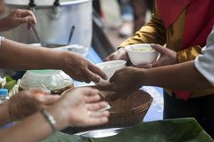 Hands of the poor receive food from the donor`s share. poverty concept. Food for the poor and homeless Help concept royalty free stock images
