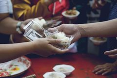 Hands of the poor receive food from the donor`s share. poverty concept.  stock photography
