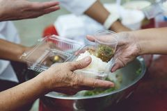 Hands of the poor receive food from the donor`s share. poverty concept.  royalty free stock photography