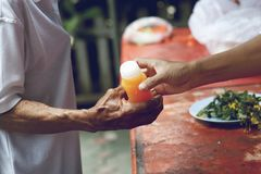 Hands of the poor receive food from the donor`s share. poverty concept.  royalty free stock images