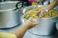 The hands of the poor receive food from the hands of the humane : the concept of relief.  stock images