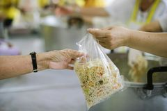 The hands of the poor receive food from the hands of the humane : the concept of relief.  royalty free stock photography