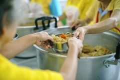 Hands-on food of the hungry is the hope of poverty : concept of homelessness. The hands of the poor receive food from the hands of the philanthropist : concept royalty free stock photography
