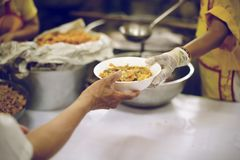 The hands of the poor receive food from the hands of the humane : the concept of relief.  stock photography