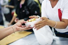 The hands of the poor receive food from the hands of the humane : the concept of relief.  stock photo