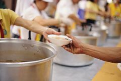The hands of the poor receive food from the hands of the humane : the concept of relief.  royalty free stock photo