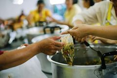 The hands of the poor receive food from the hands of the humane : the concept of relief.  stock photos
