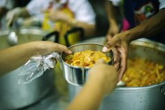 Hands-on food of the hungry is the hope of poverty : concept of homelessness. The hands of the poor receive food from the hands of the philanthropist : concept royalty free stock image
