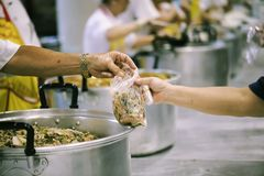 Hands-on food of the hungry is the hope of poverty : concept of homelessness. The hands of the poor receive food from the hands of the philanthropist : concept royalty free stock photos