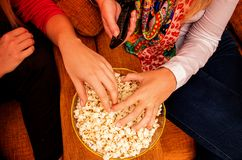 Hands on popcorn while watching movie on home cinema. Close up on hands on popcorn and remote control for home cinema evening entertainment royalty free stock photos