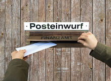 Hands post a letter into letterbox of finance office, Finanzamt. Stock Photo