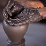 Hands of a potter. Creating an earthen jar on the circle Stock Photos