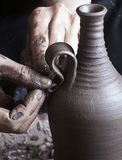 Hands of a potter. Creating an earthen jar on the circle Stock Image