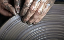 Hands of a potter. Creating an earthen jar on the circle Stock Photography