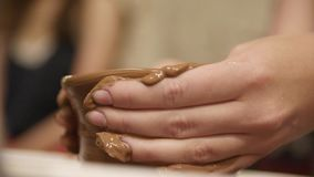 Hands of a Potter. Close-up hands of a male potter in apron molds bowl from clay. Hobby,lifestyle concept stock video