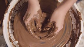 Hands of a potter. Close-up hands of a male potter in apron molds bowl from clay. Hobby,lifestyle concept stock footage