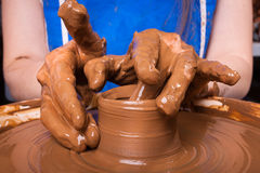 Hands of a potter, creating a clay jug on pottery wheel Stock Photo