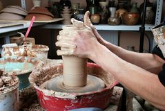 Hands of a potter, creating an earthen jar on the circle Royalty Free Stock Image