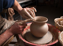 Hands of a potter, creating an earthen jar on the circle Stock Images