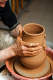 Hands of a potter, creating an earthen jar on the circle Stock Photography