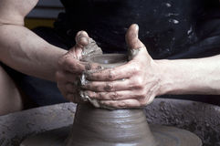 Hands of a potter. Creating an earthen jar on the circle Royalty Free Stock Image