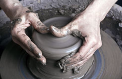 Hands of a potter. Creating an earthen jar on the circle stock images