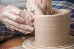Hands of a potter. Creating an earthen jar on the circle royalty free stock images