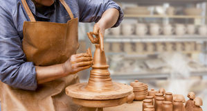 Hands of a potter, creating an earthen jar on the circle. Royalty Free Stock Images