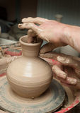 Hands of a potter, creating an earthen jar on the circle Royalty Free Stock Images