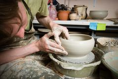 Hands of a potter, creating an earthen jar on the circle Stock Image