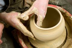 Hands of a potter, creating an earthen jar of white clay Stock Photography