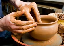 Hands of a potter, creating an earthen jar of white clay Royalty Free Stock Photo