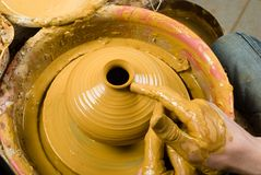 Hands of a potter, creating an earthen jar of yellow clay Stock Image