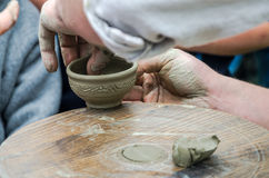 Hands of potter do a clay pot on the street at the fair Stock Images