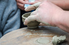 Hands of potter do a clay pot on the street at the fair Royalty Free Stock Photo