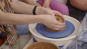 Hands of a potter. Hands of a woman potter makes on the pottery wheel clay pot.Creating an earthen jar on the circle at master class in slow motion. Hobby stock video