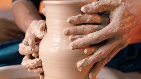 Hands of potter and his female student. Man and woman working together, creating clay product on potter wheel. Traditional pottery making, teacher shows basics stock footage