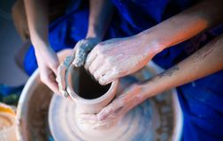 Hands of potter and his female student. Man and woman working together, creating clay product on potter wheel royalty free stock image
